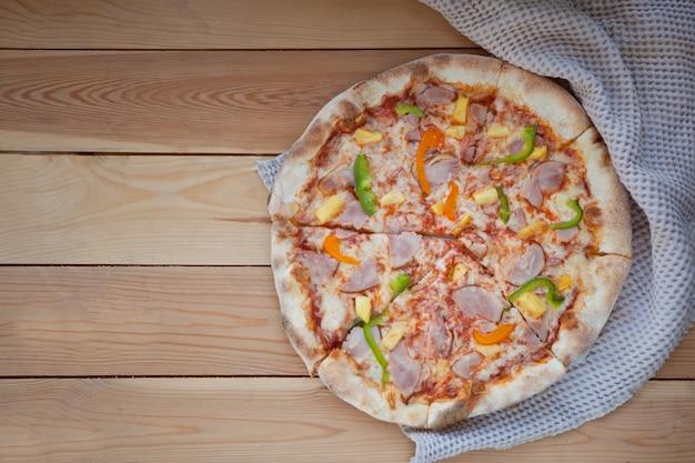 Zaokrąglona smaczna pizza z pieprzem. pokrojona domowa pyszna pizza na drewnianym rustykalnym tle
