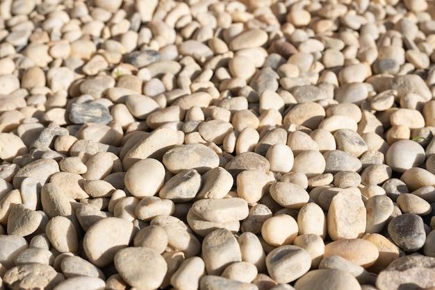 Zaokrąglone kamienie lub kamyki na tle zachodu słońca w ogrodnictwie są bardzo użytecznym sposobem na uniknięcie wzrostu trawy w pobliżu kwiatów