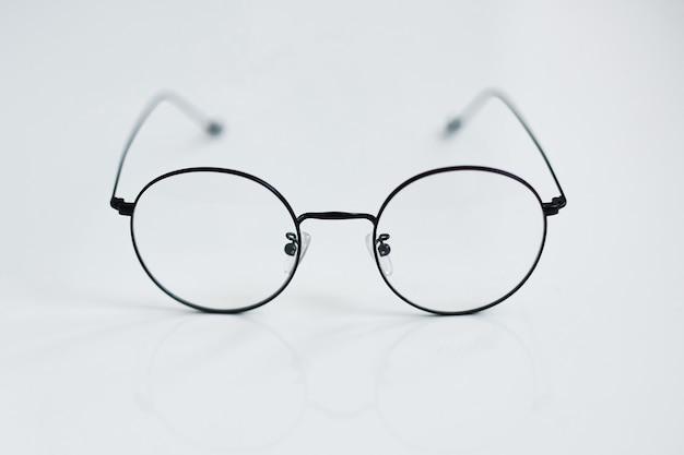 Zaokrąglone okulary vintage na białym tle. zdjęcie reklamowe okrągłych metalowych okularów. koncepcja optyczna mody. tylko okulary retro na białym tle