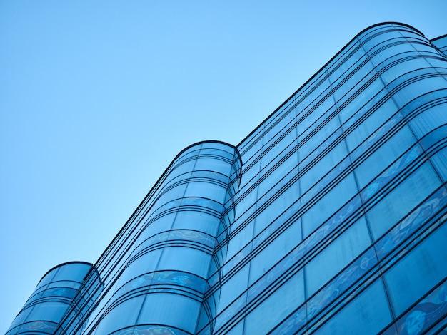 Zaokrąglony szklany budynek biurowy na tle niebieskiego nieba perspektywy