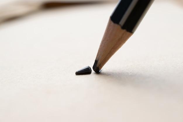 Zaostrzony ołówek nad pustą starą kartką papieru ze złamaną końcówką.