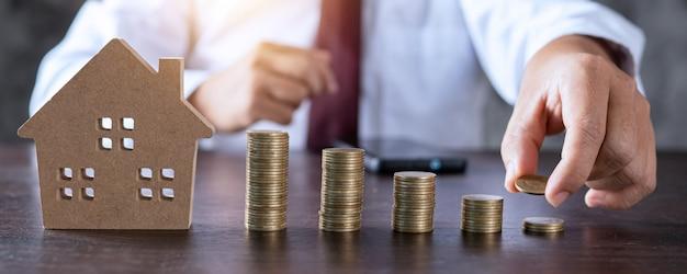 Zaoszczędź na nieruchomości, właściciel nieruchomości dostanie pieniądze na koncepcję domu, model małego drewnianego domu na stole z ręcznie ułożonymi monetami do wynajęcia lub zakupu wyżej wymienionej rezydencji za gotówkę do agencji bankowej