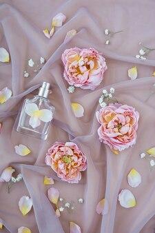 Zapach Kwiatowy. Butelka Z Rozpylaczem Na Delikatnym Różowym Materiale Z Płatkami Róż Premium Zdjęcia
