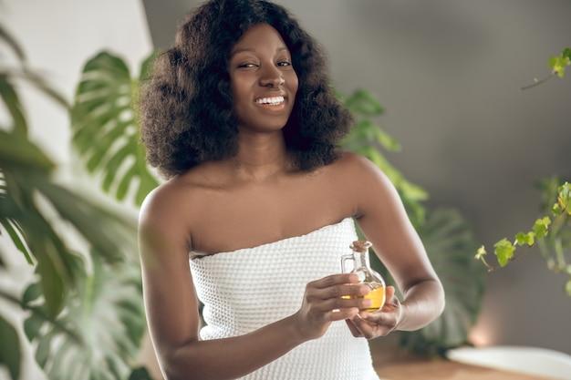 Zapach. młoda dorosła ciemnoskóra kobieta z ząbkowanym uśmiechem w białym ręczniku kąpielowym z gołymi ramionami pokazującymi zapach w szklanym słoju