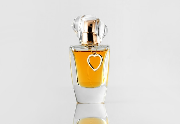 Zapach w kształcie srebrnej butelki z przodu ze złotą nasadką i żółtą linią na białej ścianie