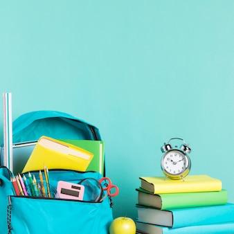 Zapakowana torba szkolna i budzik do wczesnego budzenia