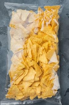 Zapakowane i przyprawione nachos oraz opakowanie z przekąskami, na szarym stole, widok z góry lub płasko