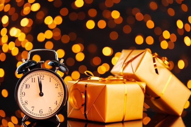 Zapakowane prezenty i budzik na złotym tle bokeh