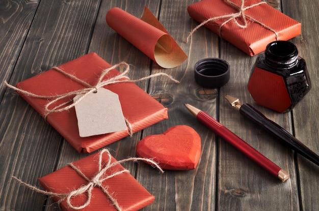 Zapakowane prezenty, papier, sznur i etykiety na brązowym drewnianym stole