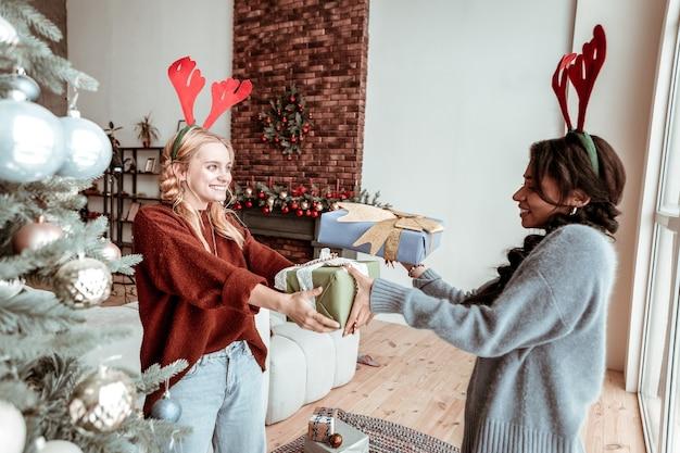 Zapakowane prezenty. przyjemne słodkie dziewczyny obdarowujące się prezentami podczas pobytu w salonie