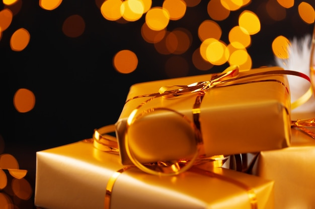 Zapakowane prezenty świąteczne na tle bokeh złote światła z bliska