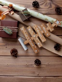 Zapakowane prezenty świąteczne w papier rzemieślniczy na drewnianym stole. proces pakowania prezentów.