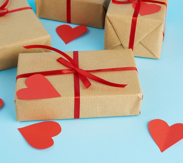 Zapakowane prezenty w brązowy papier pakowy i przewiązane czerwoną wstążką na niebieskim