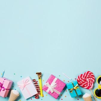 Zapakowane pudełka na prezenty; wafelek; serpentyna; okulary i lizak w kształcie serca na niebieskim tle