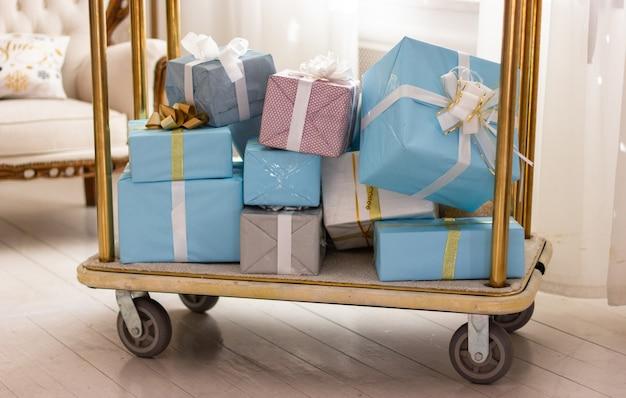 Zapakowane pudełka z prezentami świątecznymi na wózku wiele prezentów noworocznych