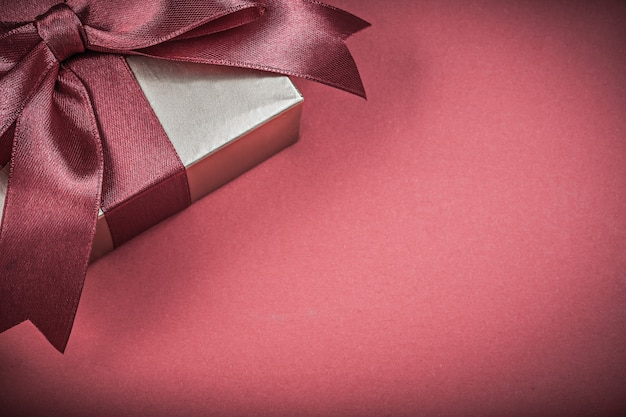 Zapakowane pudełko prezentowe na koncepcji wakacji na czerwonym tle