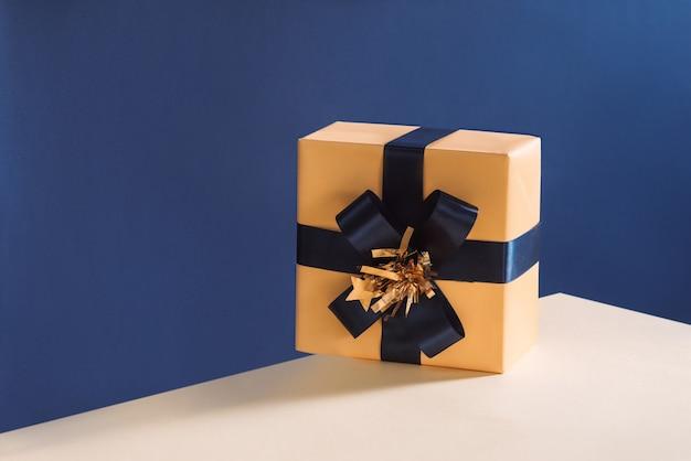 Zapakowane pudełko z kokardą niebieską wstążką na białym tle