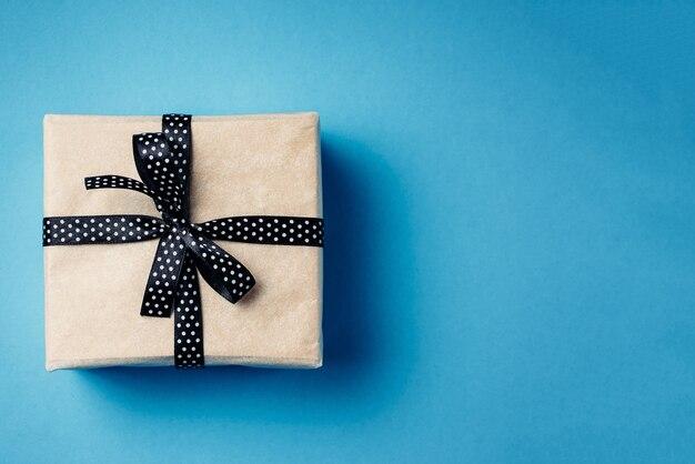 Zapakowane pudełko z kokardą wstążki na niebieskim tle z miejsca na kopię