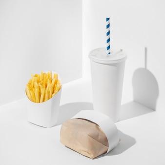 Zapakowany burger typu fast food pod wysokim kątem z pustym kubkiem i frytkami