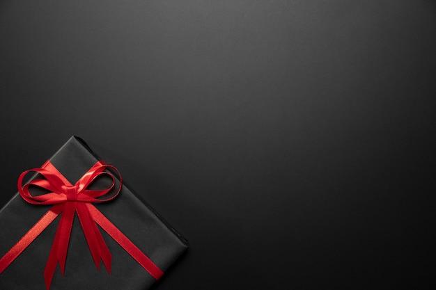 Zapakowany czarny prezent z miejsca na kopię