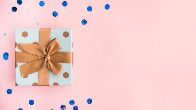 Zapakowany prezent z brązową kokardą i wstążką na pastelowym różowym tle