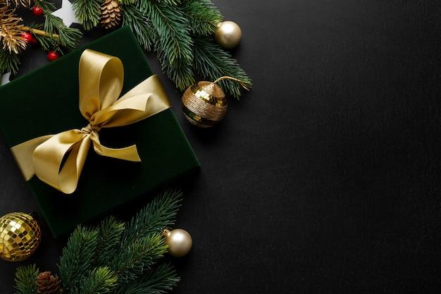 Zapakowany prezent z zieloną kokardką i bombkami na ciemnym tle.