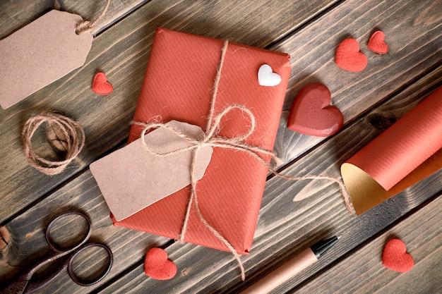 """Zapakowany prezent zawiązany sznurkiem, tekturowa metka z napisem """"happy valentine"""" i materiały do pakowania"""