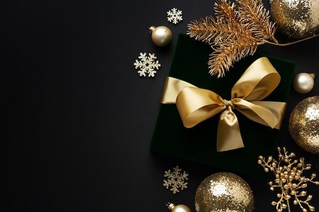 Zapakowany w złoty prezent ze złotą kokardką i bombkami na czarnym tle. flat lay.