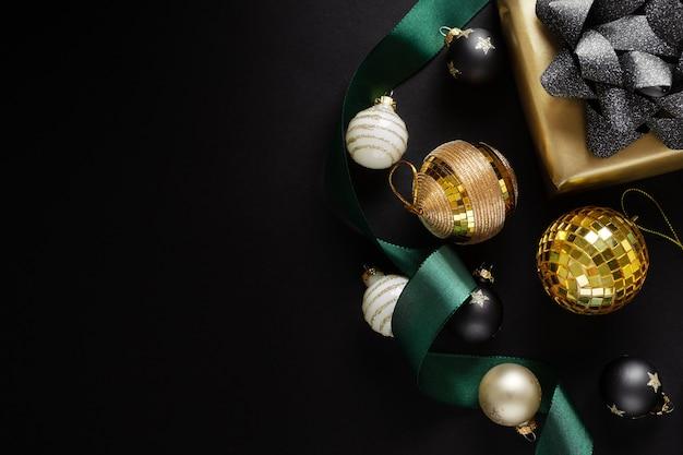 Zapakowany złoty prezent z zieloną kokardką i bombkami na ciemnej powierzchni