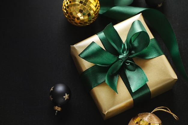 Zapakowany złoty prezent z zieloną kokardką i bombkami na czarnym tle. flat lay.