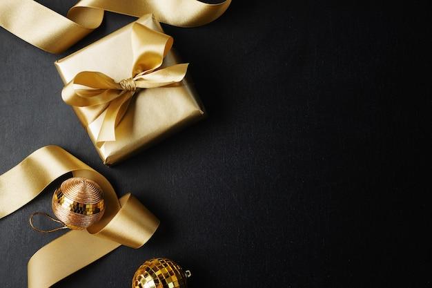 Zapakowany złoty prezent ze złotą kokardką i bombkami na ciemnym tle.