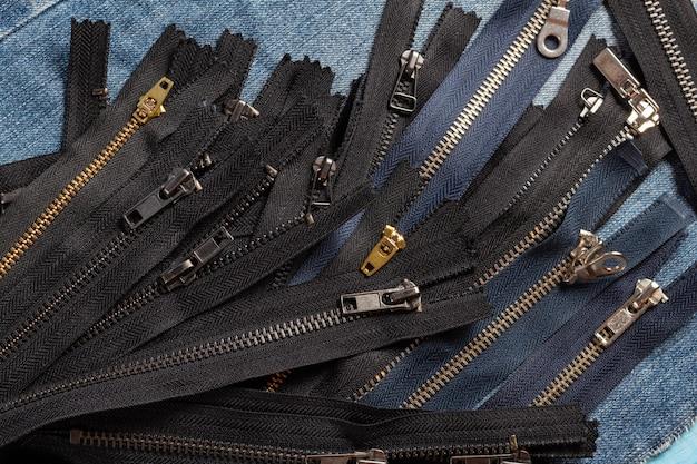 Zapakuj dużo czarnych granatowych metalowych mosiężnych pasków w paski z suwakami