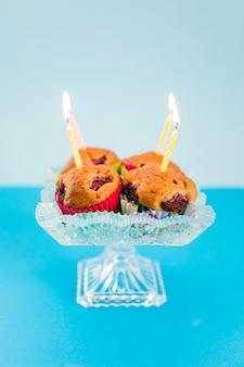 Zapalała świeczki nad cupcake na kryształowym cakestand przeciw błękitnemu tłu