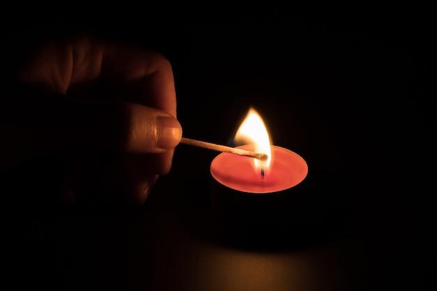 Zapalanie czerwonej świecy z zapałką w ciemności. pojęcie pamięci. czarne tło.