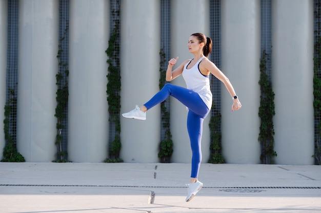 Zapalona kobieta ćwicząca na betonowej kostce, wznosząca kolana wysoko w górę