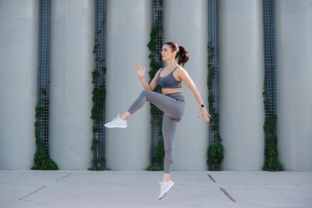 Zapalona kobieta ćwicząca na betonowym chodniku uderzająca łokciami kolanami