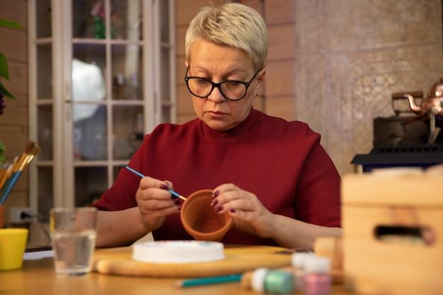 Zapalona kobieta w średnim wieku maluje doniczki w przytulnym wiejskim hobby hobby rysowania