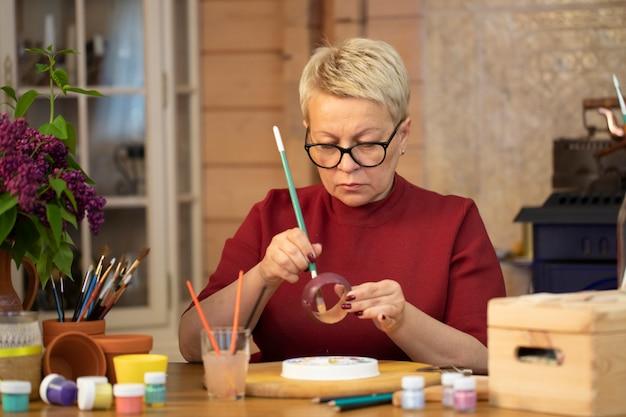 Zapalona kobieta w średnim wieku maluje drewnianą bransoletę w wiejskim domu. hobby rysunku.