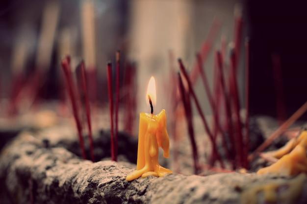 Zapalona świeca na garnku joss stick, wybrane skupienie na świecy