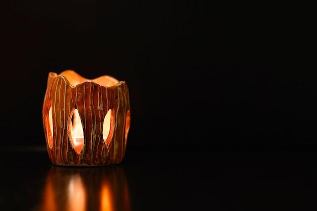 Zapalona świeca wewnątrz świecznika na czarnym tle. strzelaj światłem ze szczelin świecznika wykonanego z gliny własnymi rękami. blask świecy odbija się. miejsce na tekst