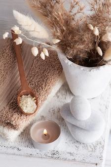 Zapalona świeca zapachowa i złociste suche kwiaty na rustykalnym tle