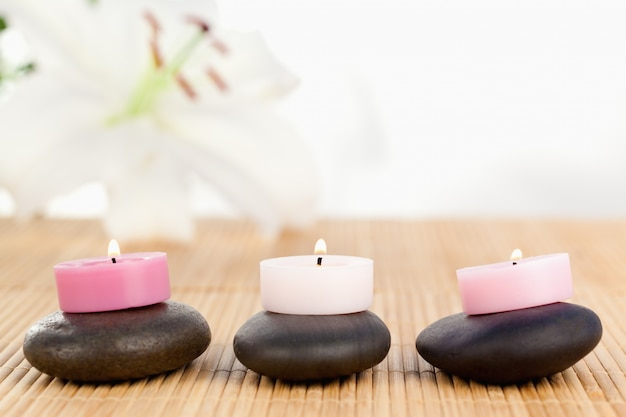 Zapalone świece na czarnych kamykach