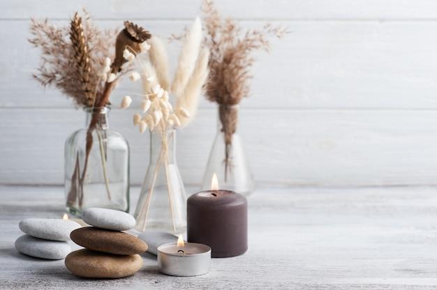 Zapalone świece zapachowe i suszone kwiaty na rustykalnym tle. aranżacja spa w stylu monochromatycznym