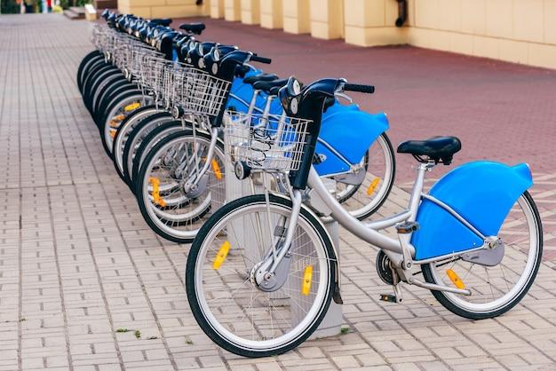 Zaparkowane miejskie srebrno-niebieskie rowery na stacji.
