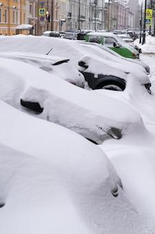 Zaparkowane samochody pokryte śniegiem na nieoczyszczonej zaśnieżonej drodze po opadach śniegu. zła pogoda zimowa, zwiększone opady i koncepcja poziomu śniegu.