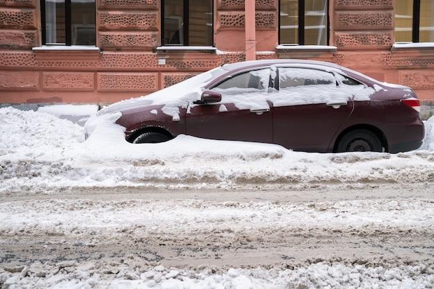 Zaparkowany samochód pokryty śniegiem na nieoczyszczonej zaśnieżonej drodze po opadach śniegu. zła pogoda zimowa, zwiększone opady i koncepcja poziomu śniegu.