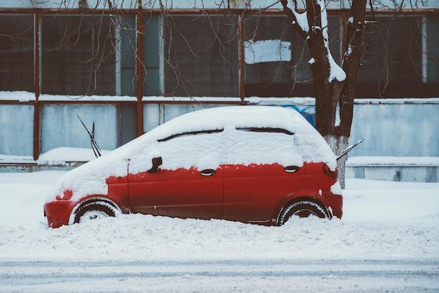 Zaparkowany samochód stoi wzdłuż drogi na śniegu