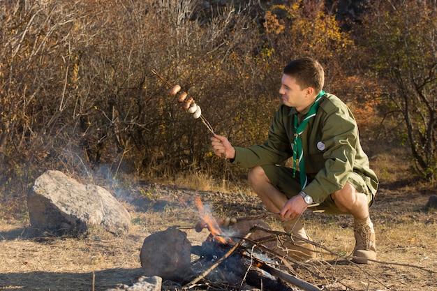 Zaparkuj strażnika lub harcerza gotującego kiełbaski nad małym otwartym ogniem na kempingu, sprawdzając, czy są ugotowane