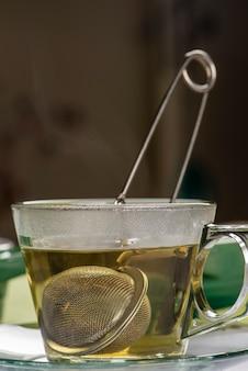 Zaparzacz z herbatą w filiżance z gorącą wodą.