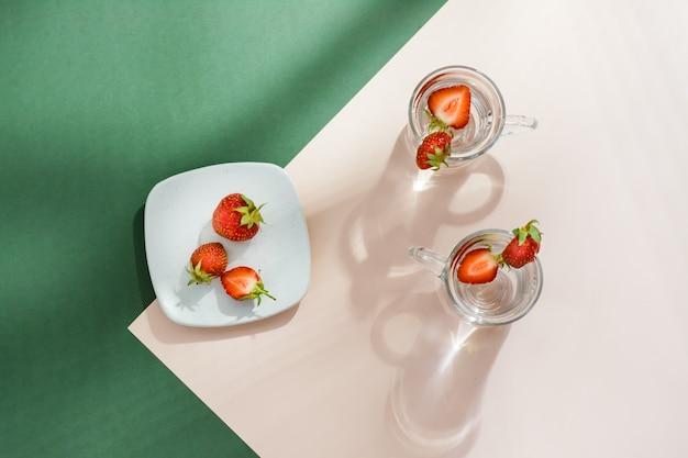 Zaparzana woda z truskawkami w szklankach i jagodami na spodku na zielono-różowym stole
